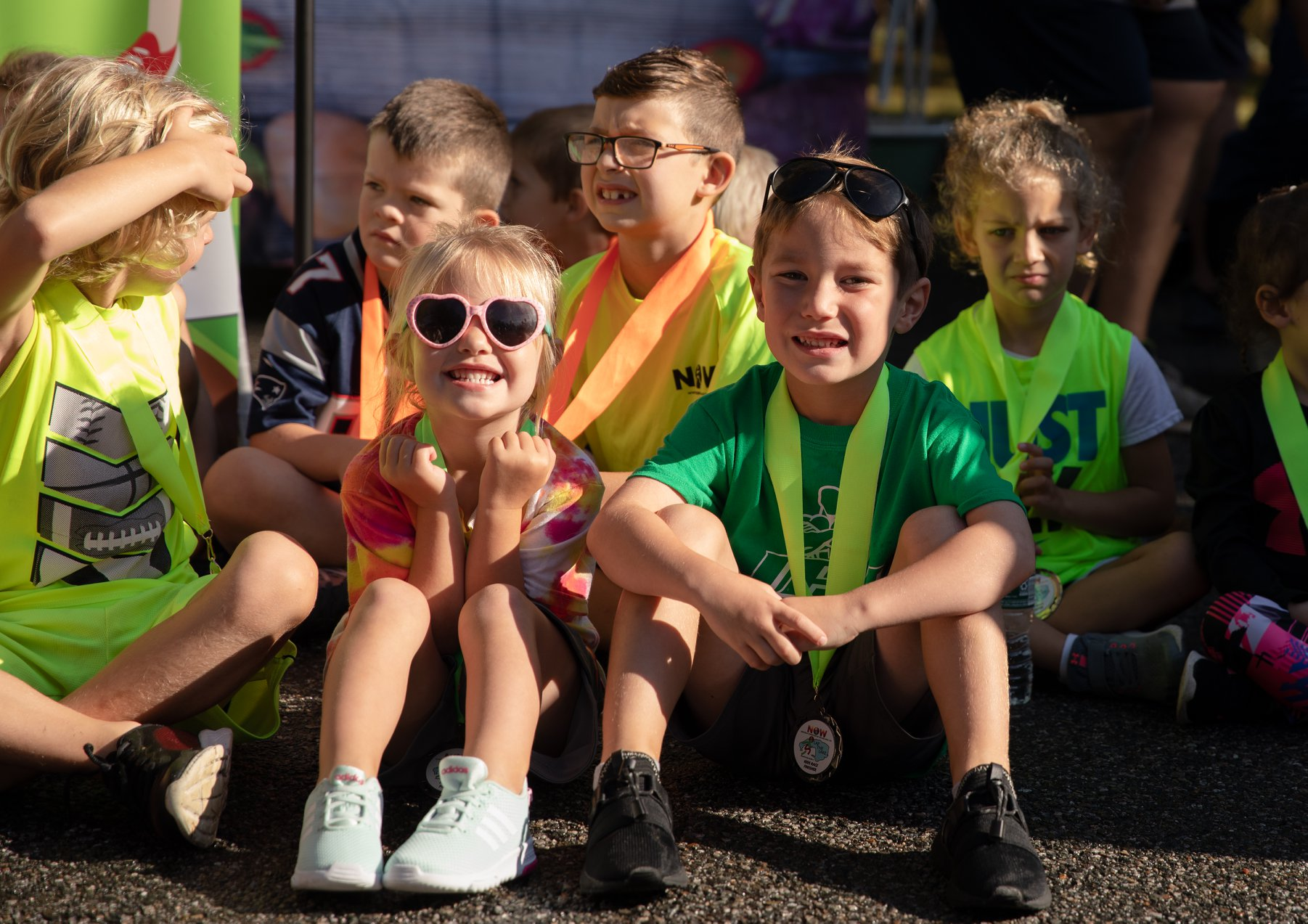 kids sitting and smiling with race medals